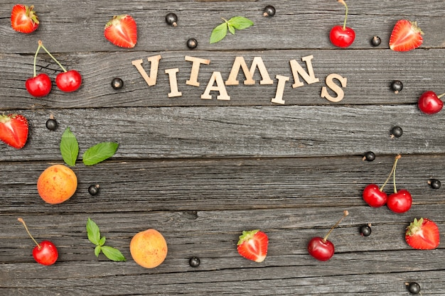 Frutas y vitaminas de inscripción sobre un fondo negro de madera