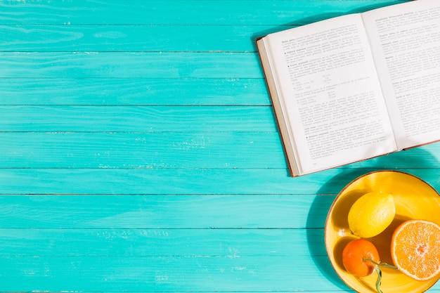 Frutero y libro sobre mesa.