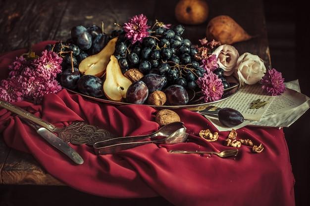 El frutero con uvas y ciruelas contra un mantel marrón