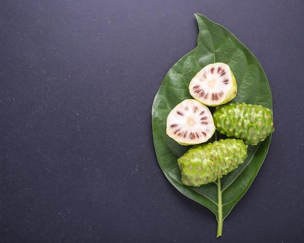 Fruto del gran morinda (noni) o árbol de morinda citrifolia y hoja verde sobre piedra negra