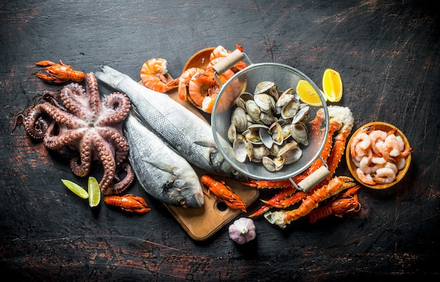 Fruto de mar. ostras, pescado fresco, camarones, pulpo y cangrejo con rodajas de limón. en rústico oscuro
