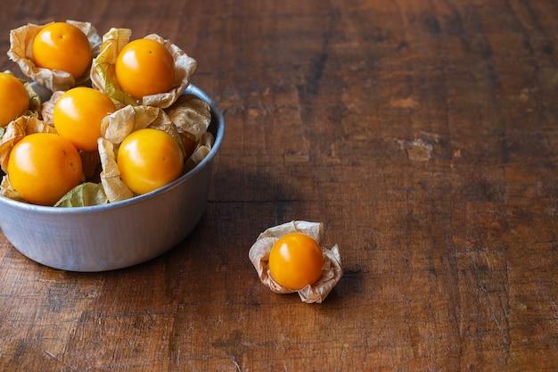 Fruto de uchuva en un recipiente sobre una mesa de madera