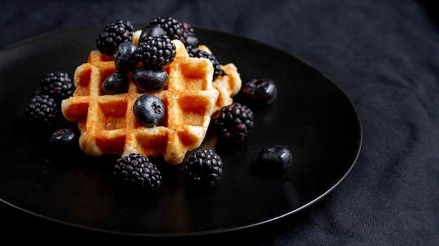 Frutos del bosque negro en waffles