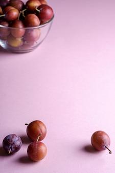 Frutos de ciruela dulces maduros dispersos cerca del recipiente de vidrio con ciruelas sobre fondo rosa, luz suave, espacio de copia, enfoque selectivo