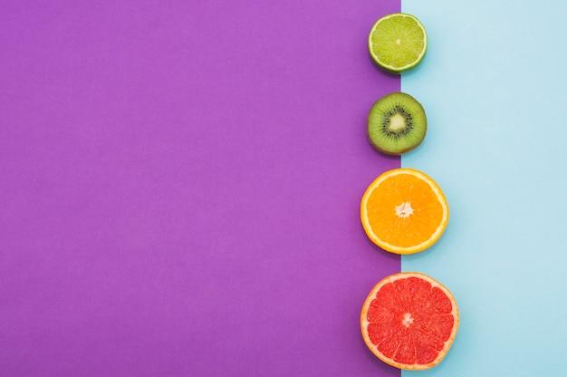 Frutos cítricos a la mitad; kiwi en la frontera de doble fondo