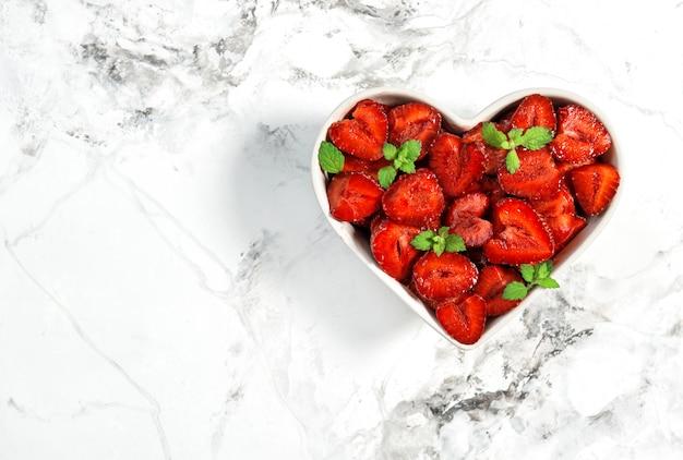 Frutos de fresa en un tazón en forma de corazón