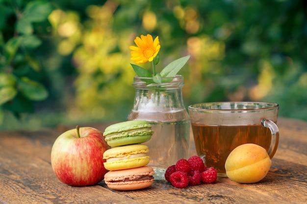 Frutos maduros de manzana, albaricoque y frambuesas, flor de caléndula con tallo en un frasco de vidrio.