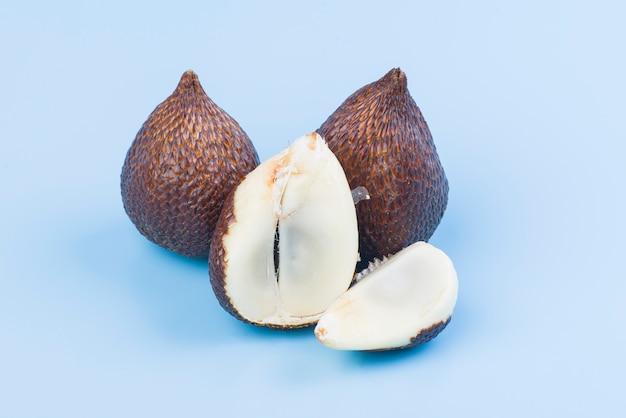 Frutos de palma espinosa o salak, frutas tropicales sobre fondo azul.