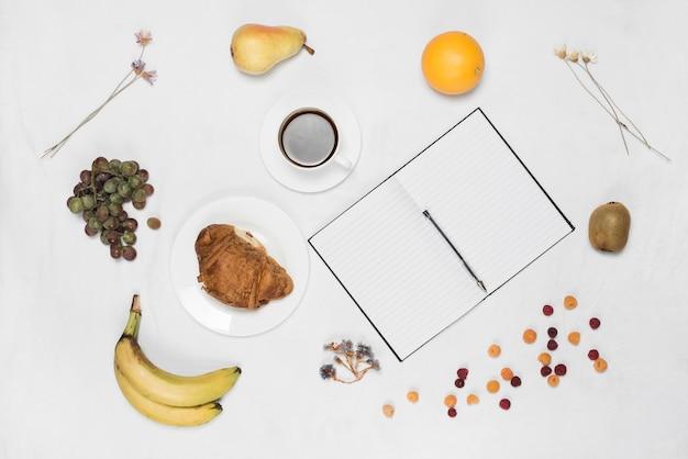 Frutos sanos; café; croissant y pluma con cuaderno de una sola línea en blanco sobre fondo blanco