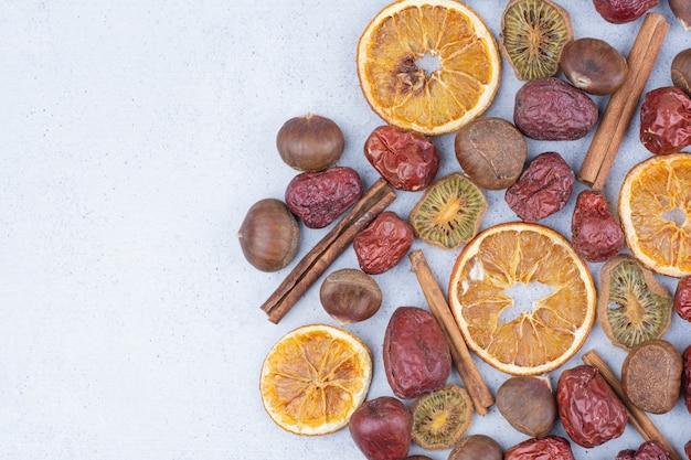 Frutos secos, canela en rama y castañas sobre superficie de mármol.
