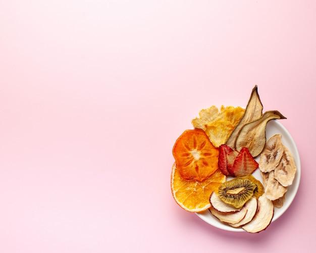Frutos secos chips sobre un fondo rosa.