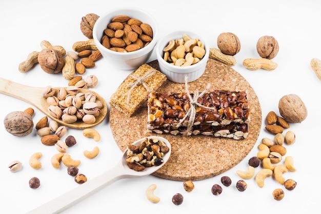Frutos secos, energía, barra e ingredientes sobre fondo blanco