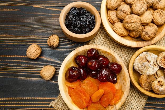 Frutos secos higos, albaricoques, ciruelas y nueces en mesa de madera