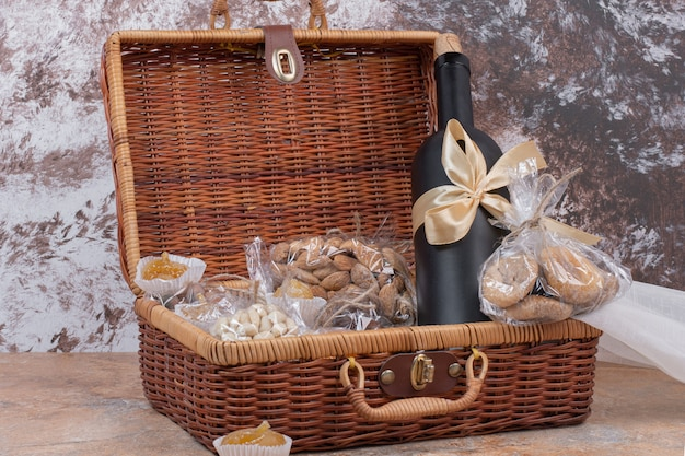 Frutos secos y nueces en bolsa de madera con botella de vino.