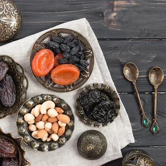 Frutos secos y nueces; fechas para ramadan con cucharas sobre el escritorio de madera