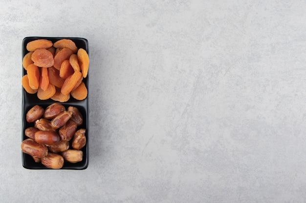 Frutos secos en el recipiente sobre la superficie de mármol