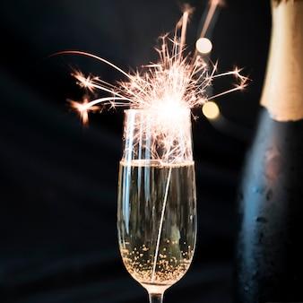 Fuego de bengala ardiendo en copa de champán