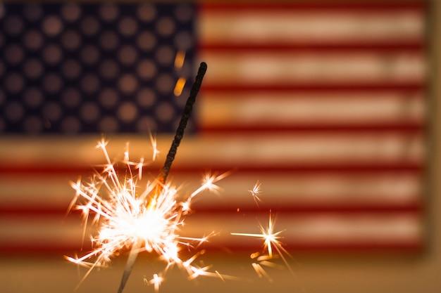 Fuego de bengalas contra la bandera de estados unidos desenfocada