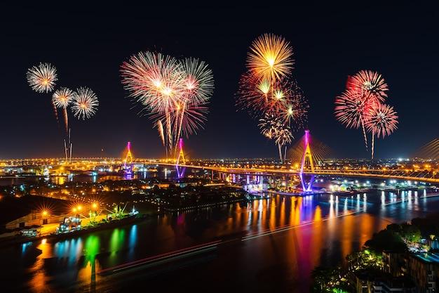 Fuegos artificiales celebrando sobre el puente colgante de bhumibol en la noche en la ciudad de bangkok, tailandia