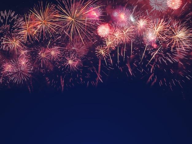 Fuegos artificiales coloridos en el fondo de cielo negro con espacio libre para texto