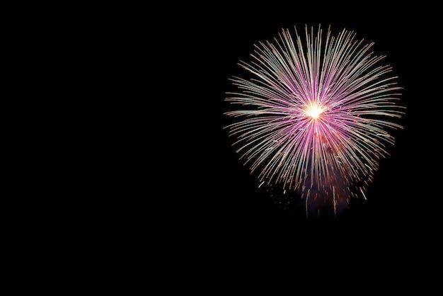 Los fuegos artificiales exhiben para la celebración en fondo negro, concepto del día de fiesta del año nuevo.