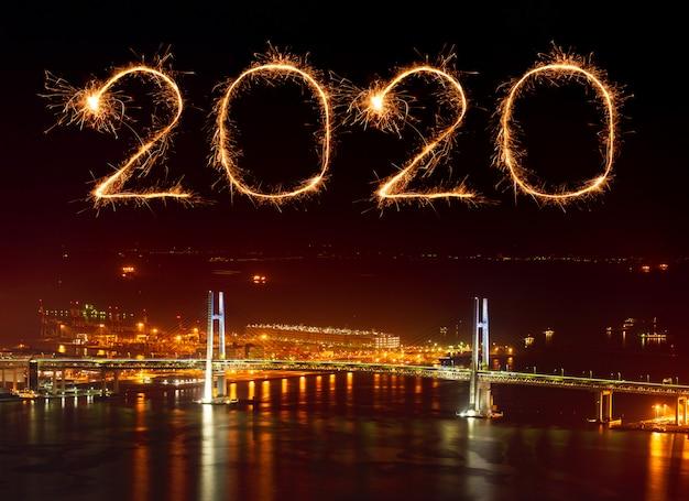 Fuegos artificiales de feliz año nuevo 2020 sobre el puente de la bahía de yokohama en la noche, japón