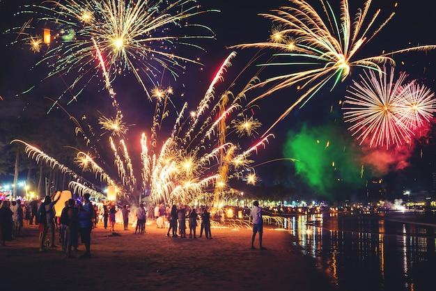 Fuegos artificiales con siluetas de personas en eventos de vacaciones. fuegos artificiales de año nuevo en la playa. los viajeros y las personas celebran el día de año nuevo en kamala beach phuket, tailandia.