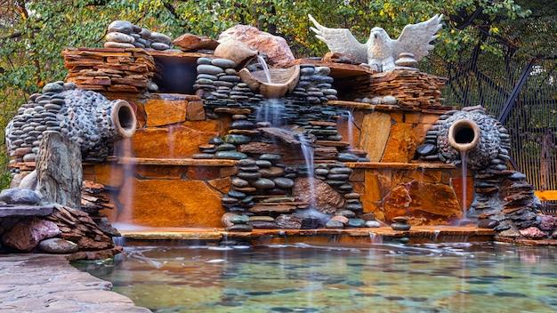 Fuente, hecha de diferentes piedras, el agua fluye desde varias jarras de arcilla en una gran piscina con agua clara.