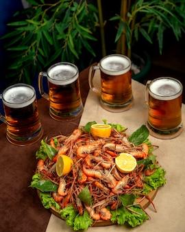 Una fuente de langostinos fritos servidos con jarras de cerveza
