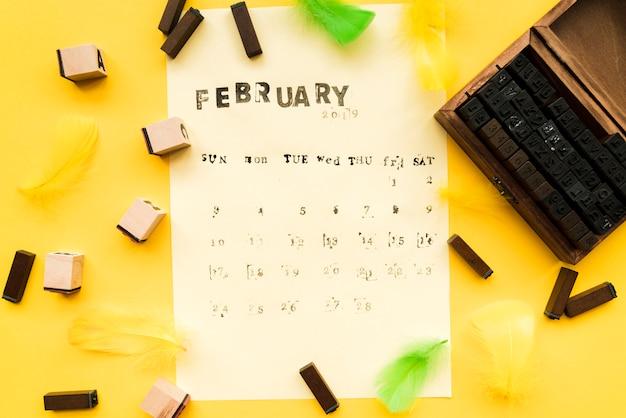Fuente de la máquina de escribir; bloques tipográficos y plumas sobre papel sobre el fondo amarillo.