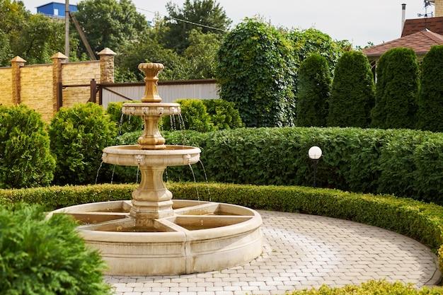 Fuente con pequeños ángeles y demonios pequeña cascada antigua en el jardín cayendo gotas de primer plano