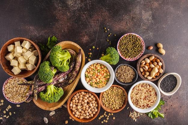 Fuente de proteína vegana. tofu, frijoles, garbanzos, nueces y semillas sobre un fondo oscuro, vista desde arriba, copia espacio.