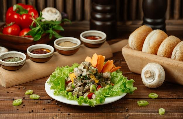 Una fuente saludable de ensalada que contiene champiñones, zanahorias picadas, cerezas y hojas de ensalada.