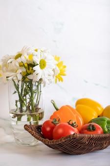 Fuente de tomate pimiento y un florero
