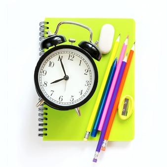 Fuentes de escuela y reloj de alarma coloridos en blanco.