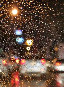 Fuera de foco del atasco de tráfico en la noche lluviosa vista desde el parabrisas de un automóvil con gotas de lluvia