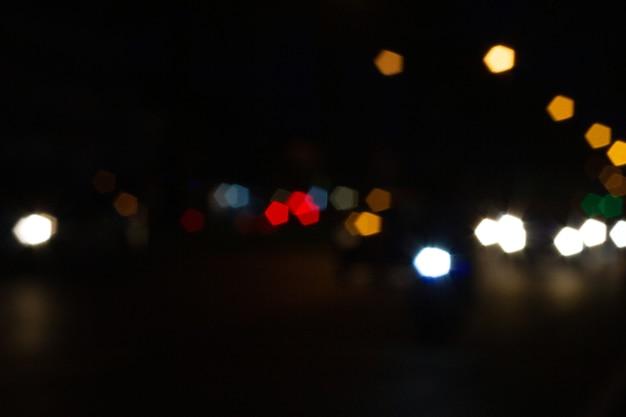 Fuera de foco hermoso bokeh borroso brillante de coches y semáforos en la noche.