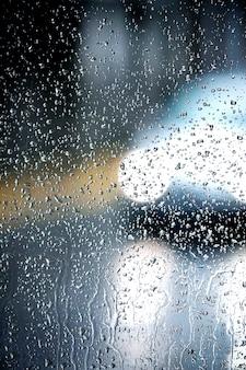 Un fuera de foco luces de un coche y un vaso con muchas gotas de lluvia.