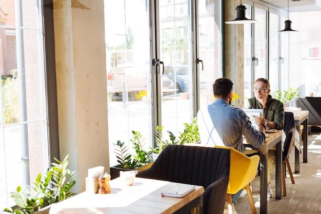 Fuera de la oficina. hombres guapos agradables sentados en el café mientras discutían el trabajo fuera de la oficina