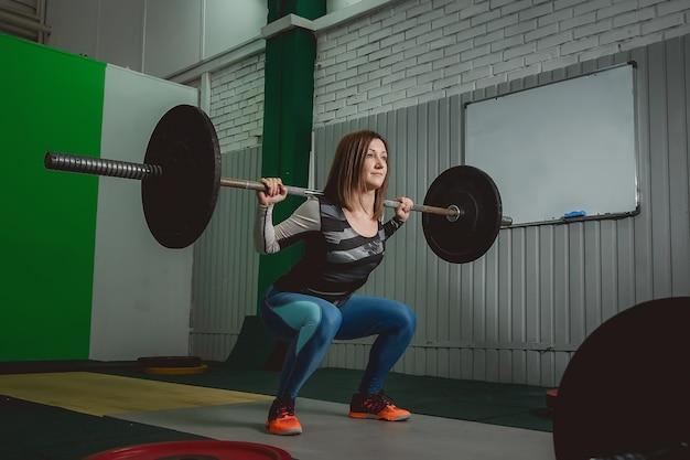 Fuerte barra de elevación de la mujer como parte de la rutina de ejercicios crossfit