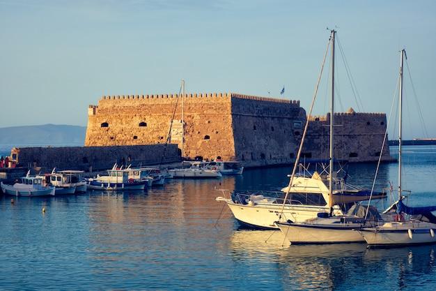 Fuerte castillo veneciano en heraklion y barcos pesqueros amarrados, la isla de creta, grecia en la puesta de sol