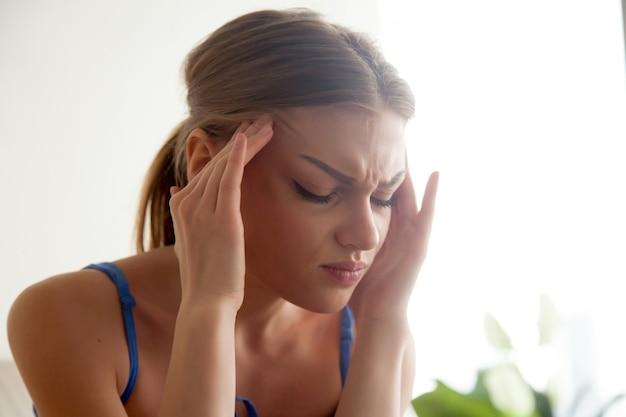 Fuerte concepto de dolor de cabeza, mujer joven masajeando templos, sufrimiento.