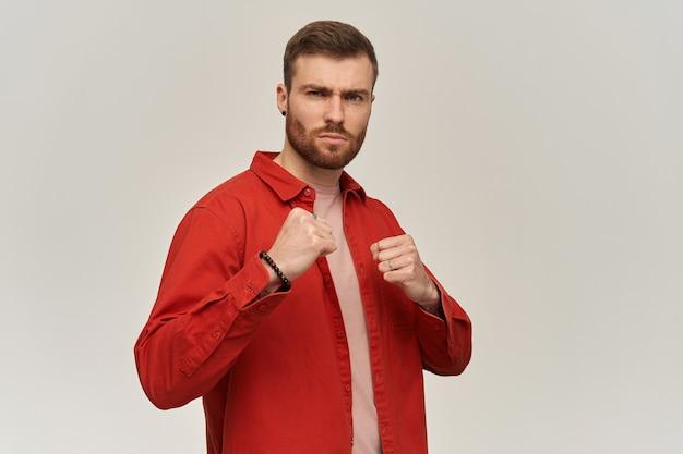 Fuerte y guapo joven barbudo con camisa roja mantiene los puños frente a él y listo para luchar por la pared blanca