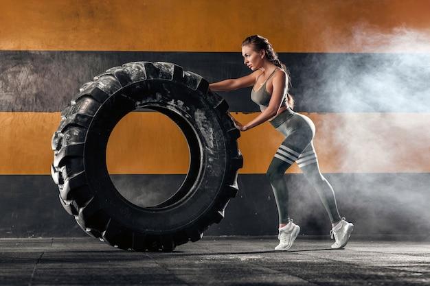 Fuerte joven atlética levantando un neumático grande en el fondo oscuro del gimnasio.