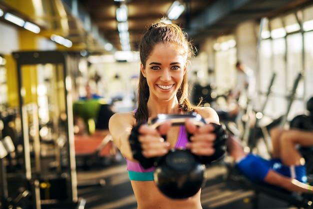 Fuerte joven forma adorable chica fitness haciendo ejercicio de brazo con pelota kettler delante de ella