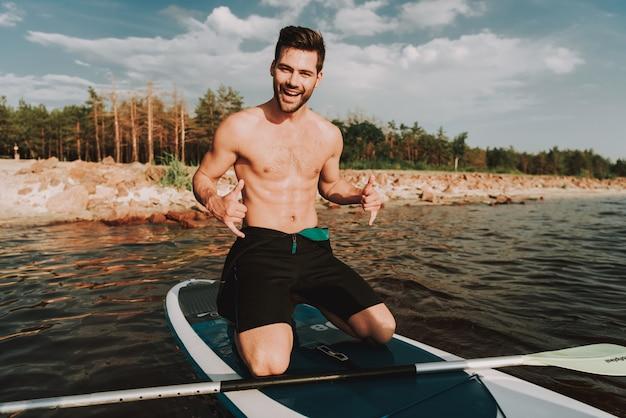 Fuerte joven macho en traje de surf de remo con paleta.