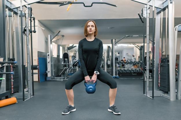Fuerte mujer joven fitness entrenamiento con pesas pesadas
