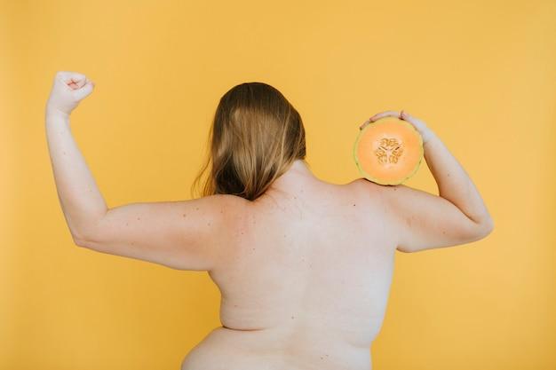 Fuerte mujer rubia sosteniendo un melón cantalupo