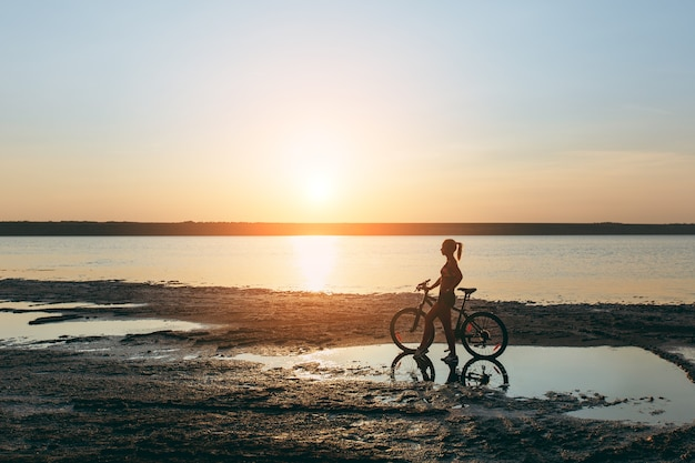 La fuerte mujer rubia con un traje colorido se encuentra cerca de la bicicleta en el agua al atardecer en un cálido día de verano. concepto de fitness.