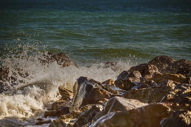 Fuerte ola de mar late en las rocas.